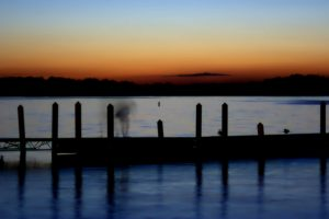 A sunset by Lake Mendota in Madison, Wisconsin, where the shadow of a woman dances on a dock.