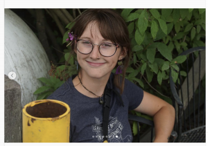Sarah Grossman is a woman with long, braided, brown hair; light skin; and glasses, and she's holding a yellow coffee cup standing out by some leaves.