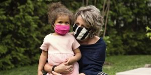 A young child with medium skin, curly brown hair, and a pink face mask, being held by an older woman with silver hair, light skin, and a black-and-white striped face mask.