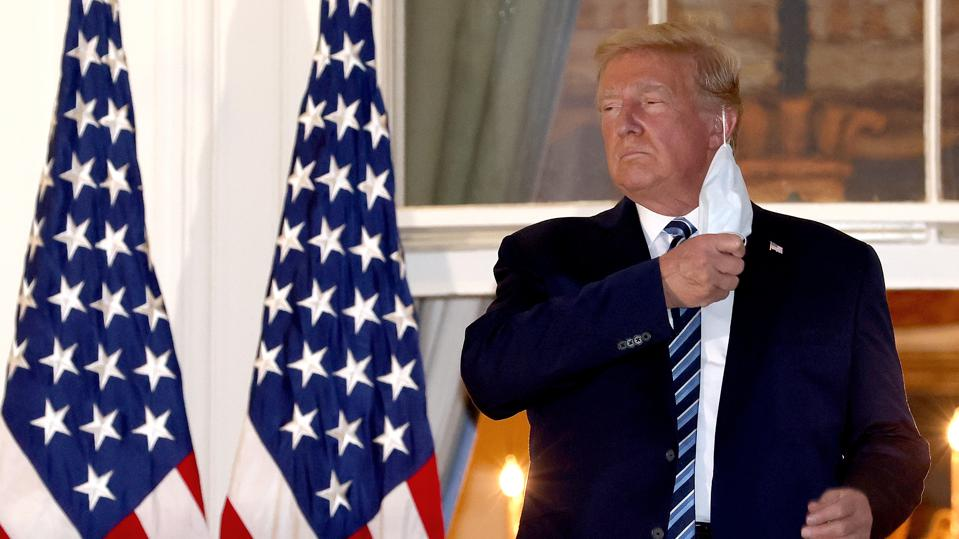 President Trump has blonde hair and fake tanned skin. He appears tired in front of two flags on the White House balcony, wearing a suit jacket and striped tie, and is removing a thin surgical mask from his face.