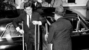 A black and white photograph of President Kennedy arriving from a limo with crutches. Kennedy has light skin and dark hair. An aide, with his back turned, is opening the limo door.