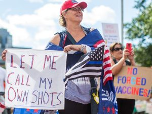 """People protesting against vaccines that nobody is forcing them to get. A woman with light hair and skin wears Blue Lives Matter paraphernalia and holds a sign that says """"LET ME CALL MY OWN SHOTS"""", while another woman with light skin and hair in the background holds up a red phone and a sign that says """"NO FORCED VACCINES""""."""