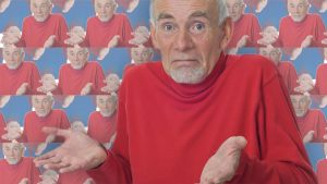 """Professor Mike Baldwin of the """"guess I'll die"""" meme. Dr. Baldwin wears a red long sleeve shirt and he is a man with pale skin and white hair and beard. He is shrugging, and the picture of him shrugging is tiled in the background too."""